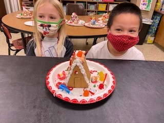 "Kindergartner's from Mrs. Demaray's class practiced team work, ""lots"" (and lots) of patience and effort to create their gingerbread houses today!  They are pretty proud of their masterpieces!❤️💚"