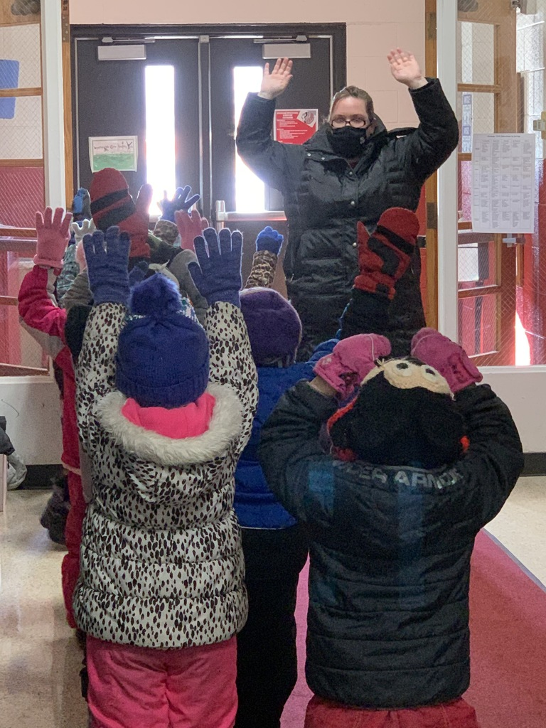 Mittens on?  Tiffany Bredman and para educator Ruth Kuehn encourage preschoolers to be self sufficient as the get on their winter gear for recess. Learning to zip their own coats and put on mittens is a skill to be learned.