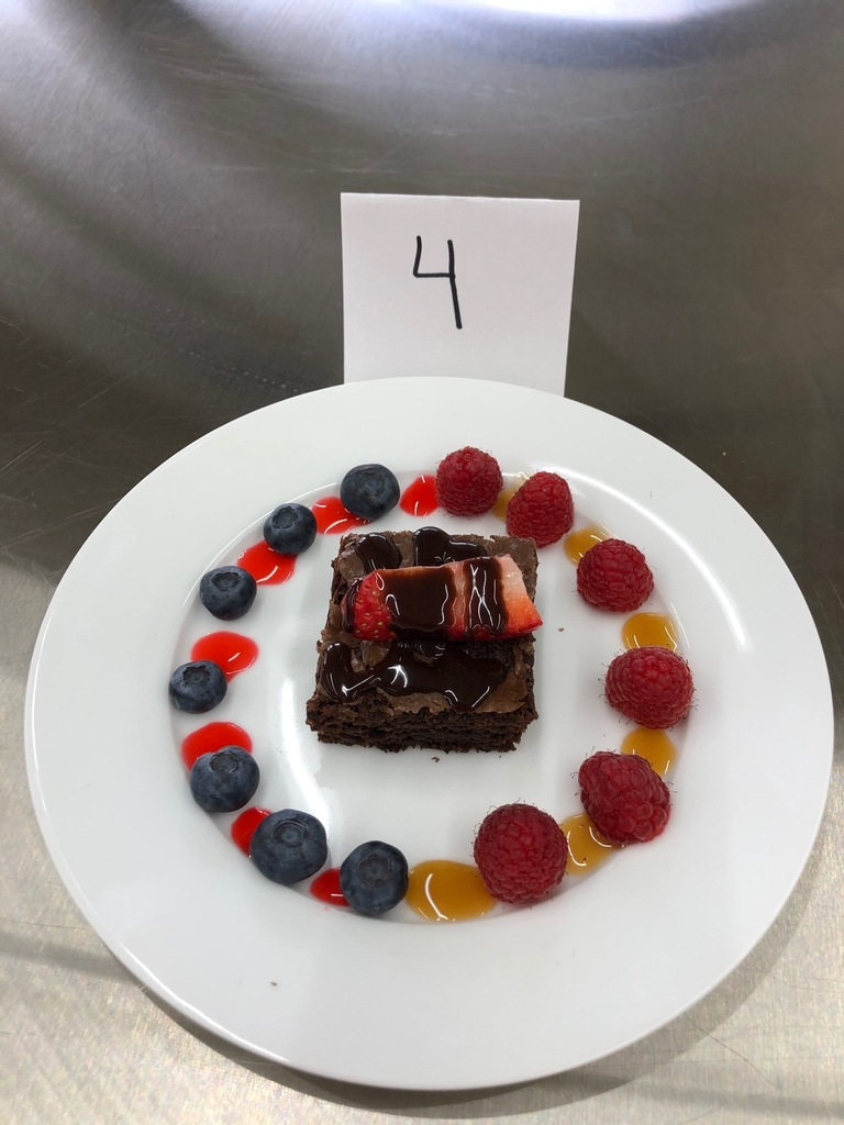 "Please vote for  Advanced Foods' garnished brownies. They learned about the rules of ""plating.""  Vote for only ONE by writing the number in the comment line.  Thank you, Mrs. Schmitt   The Advanced Foods Class also had to write a description and name their brownie as it would be on a menu for a new restaurant, so we did a Language requirement with this assignment."