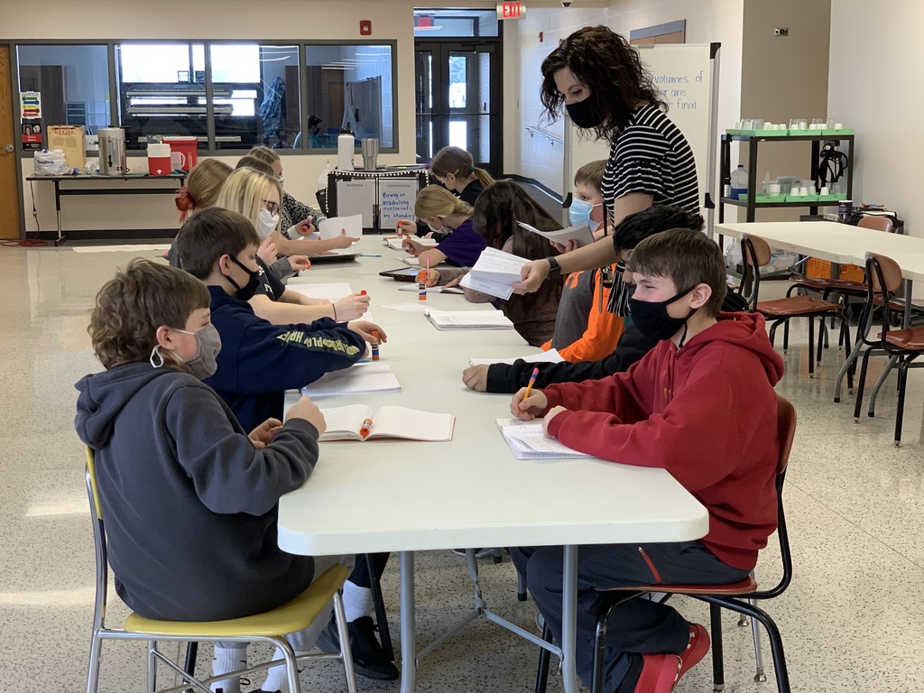 When we mix hot water and cold water, what happens to the kinetic energy?  Mrs. Sinnwell's science students prepare for a lab by gluing lab workbook forms, discussing in the groups and predicting what will happen.