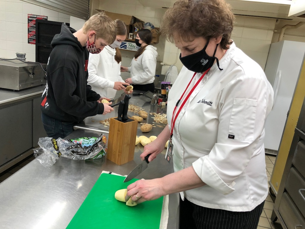 "Mrs. Schmitt is helping a group in Foods II's fruit & vegetable lab. All of their dishes turned out well! They chose their recipes: apple muffins, mashed potato cups, blueberry pancakes & waffles, and a vegetable stir-fry.  ""The students are really improving their culinary skills!"" said Mrs. Schmitt"